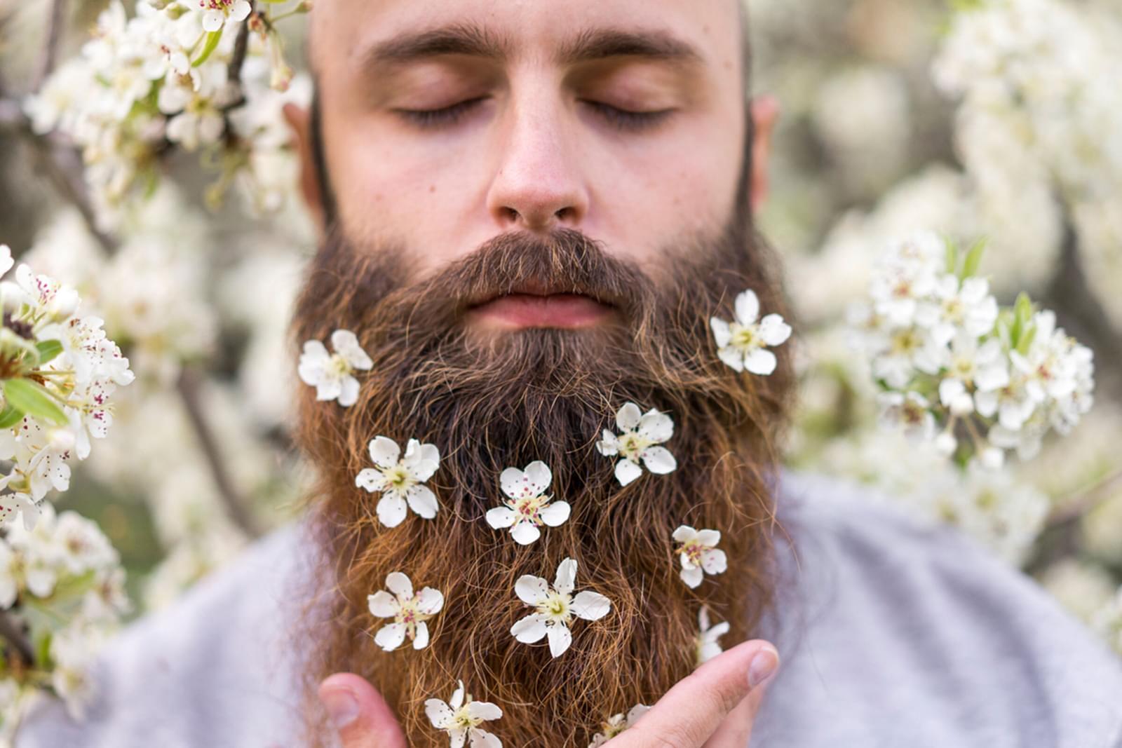Bearded gentlemen in a sleeping pose with flowers in his beard