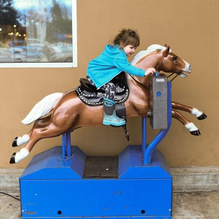 Little girl riding a automated horse machine