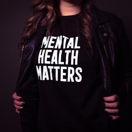 female wearing a black shirt reads mental health matters