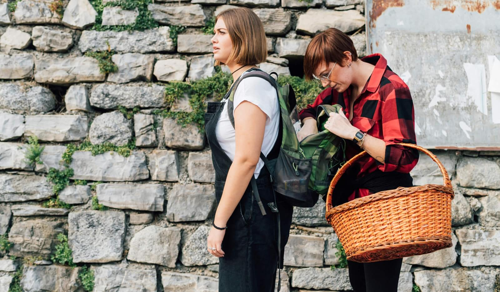 2 females working in front of a cobbled wall, one with a hand basket