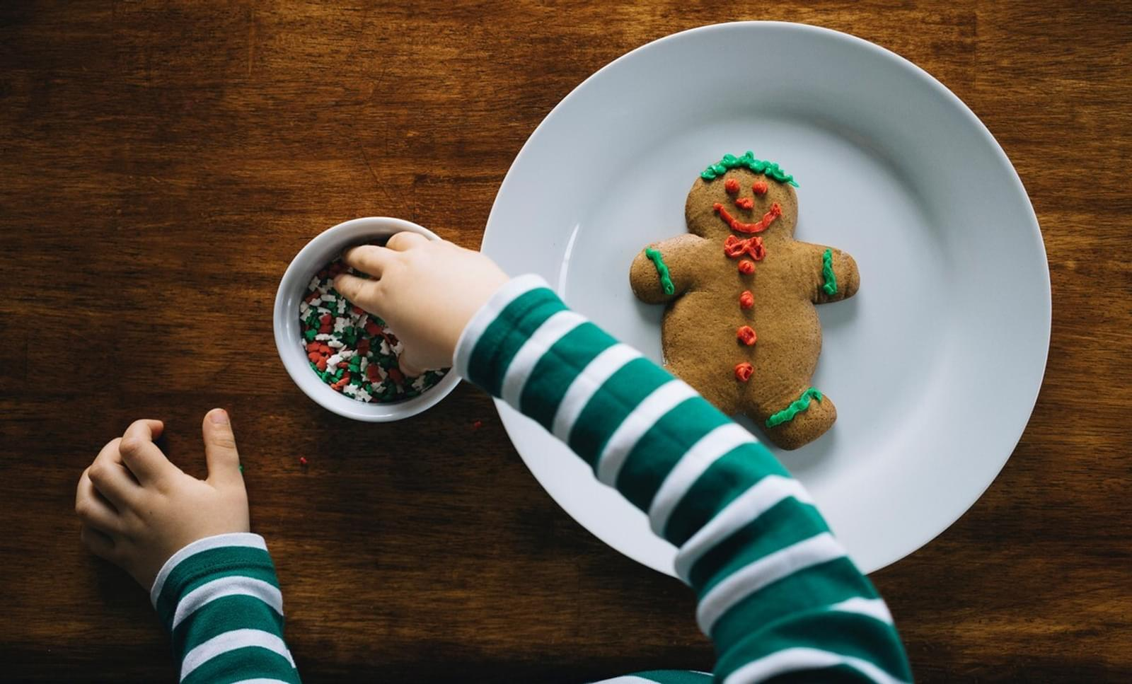 child decorating a gingerbread man