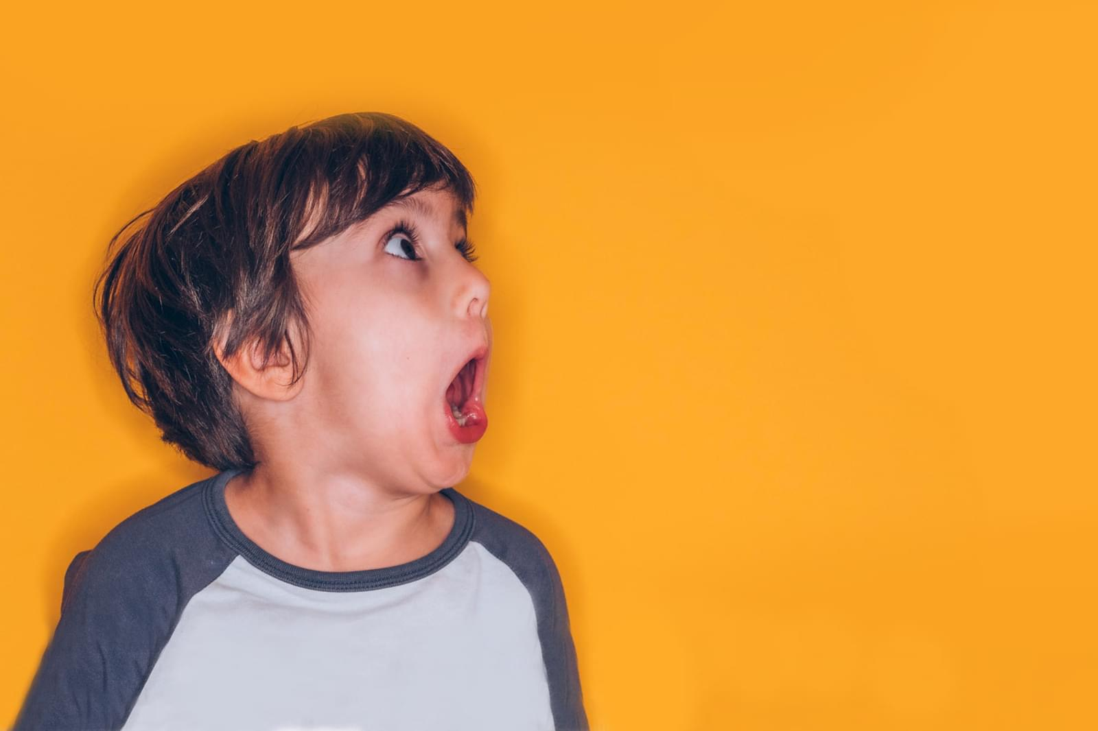 boy shouting on a yellow background