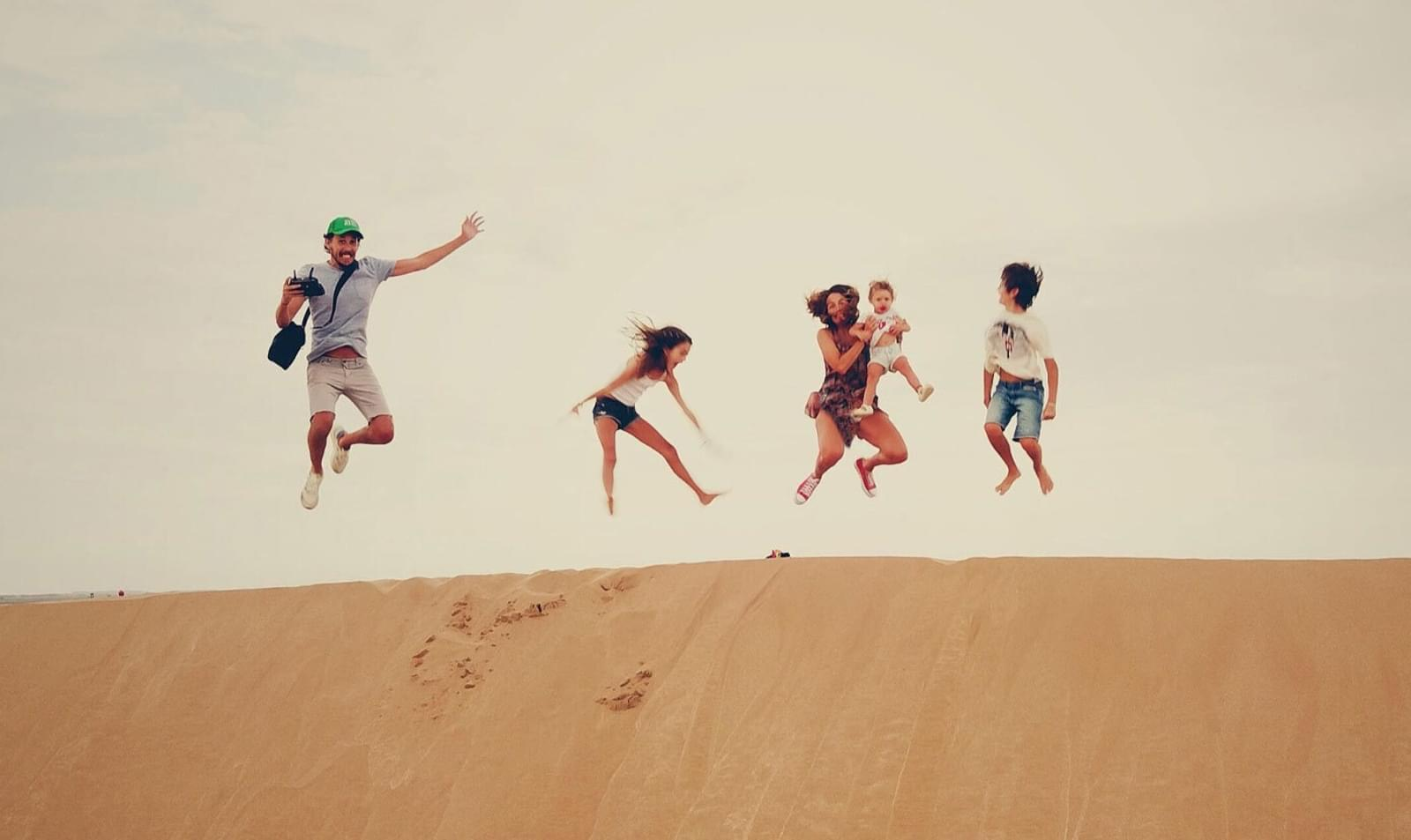 family jump with jumps in the sand dune