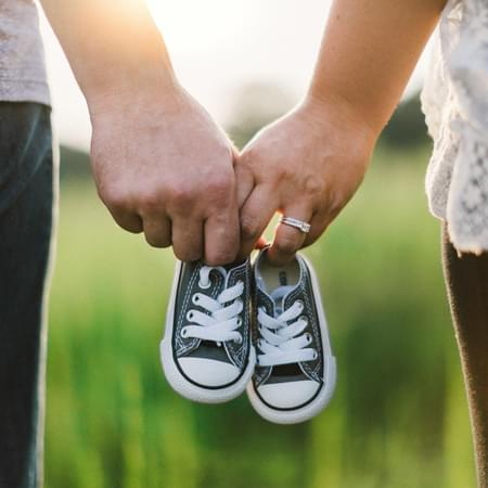 male and female holding childrens shoes