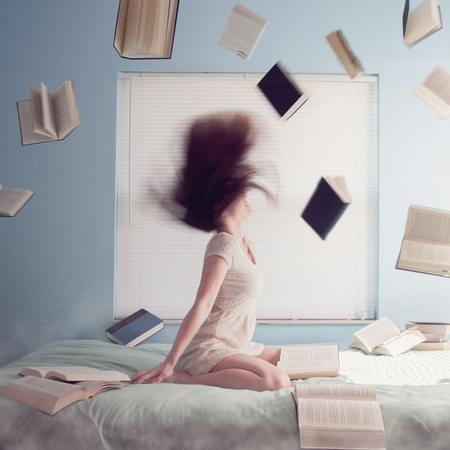 Girl throwing hair back surrounded by books