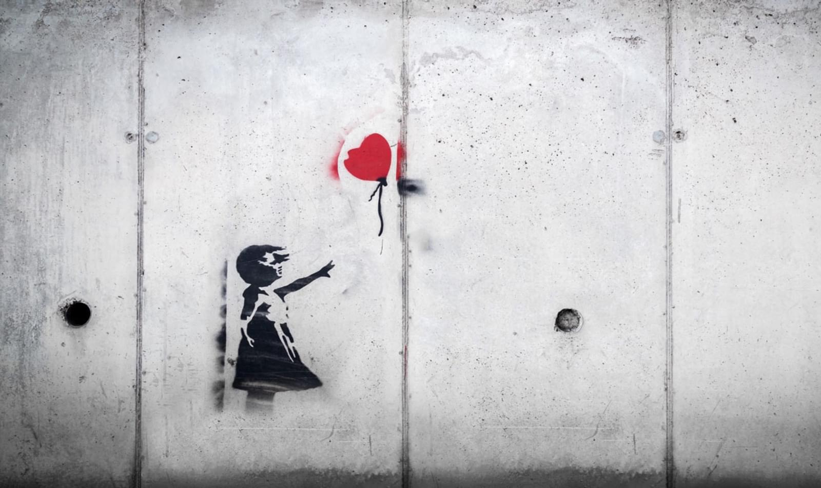 Gray wall with a silhouette of a girl losing a red balloon
