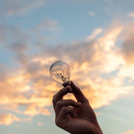 hand-holding-lightbulb-in-front-of-sky
