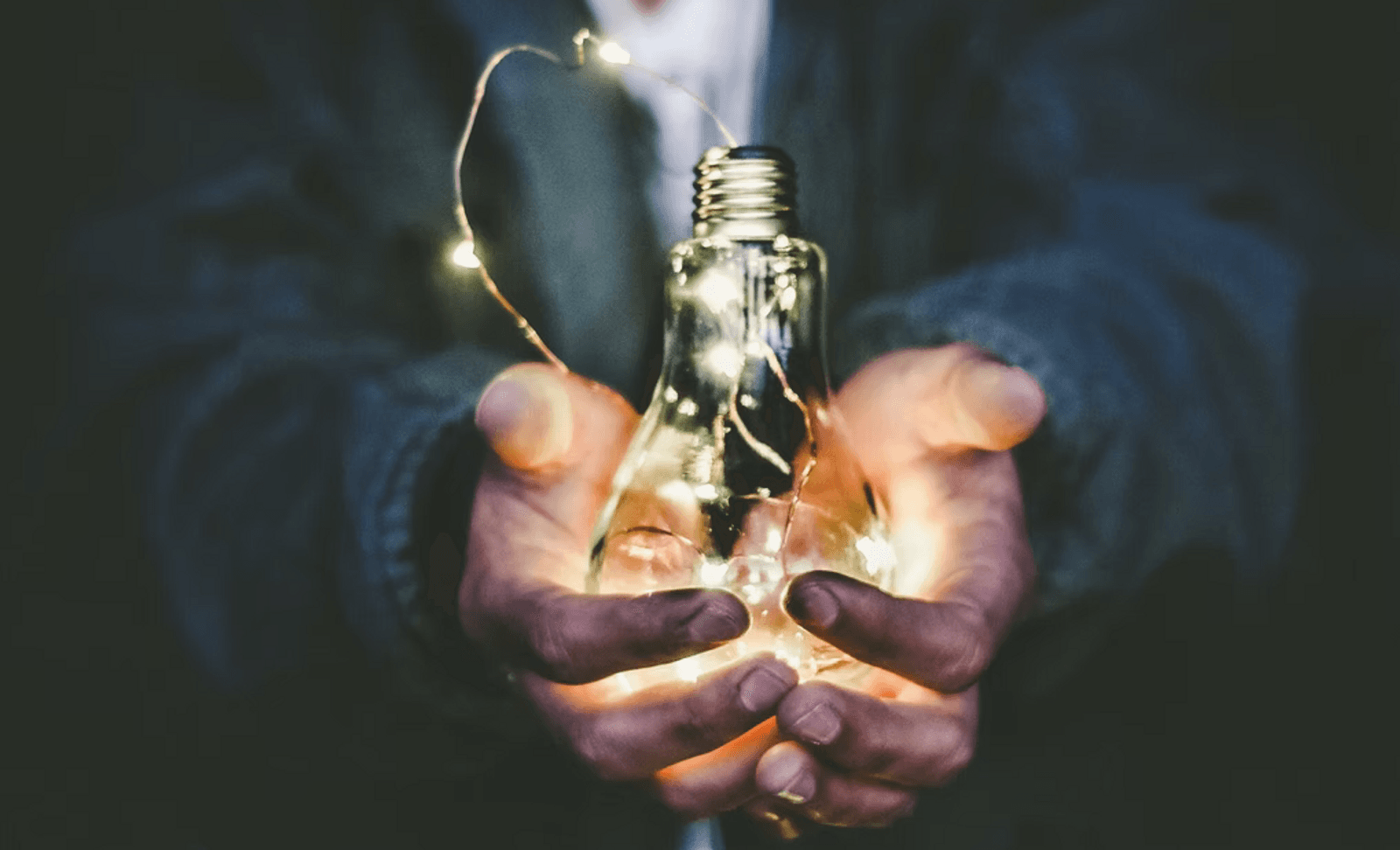 hands-holding-lightbulb-filled-with-fairy-lights