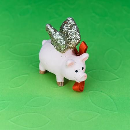piggy bank with wings and a red bow
