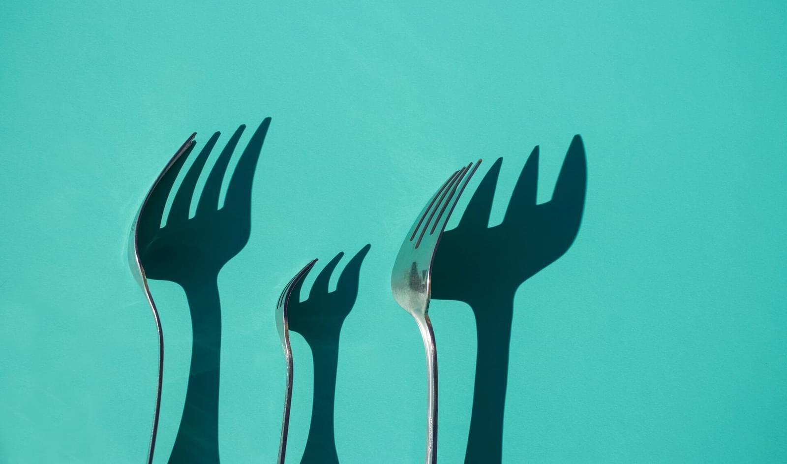 three forks in front of teal background