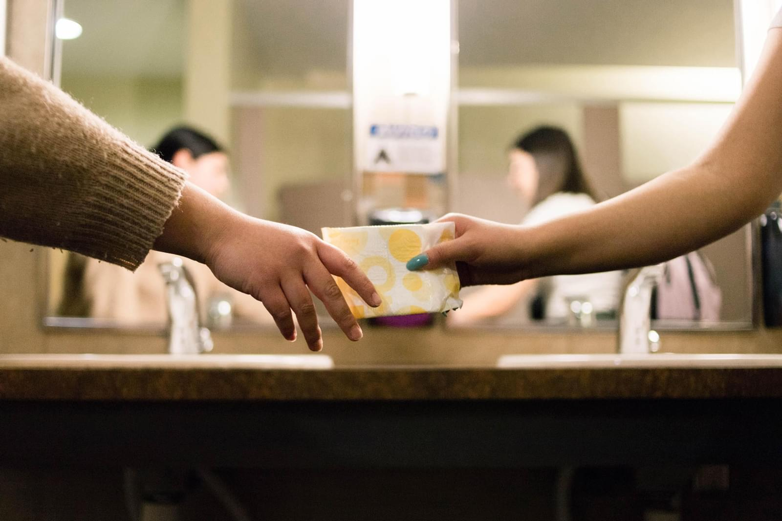 two hands passing sanitary products