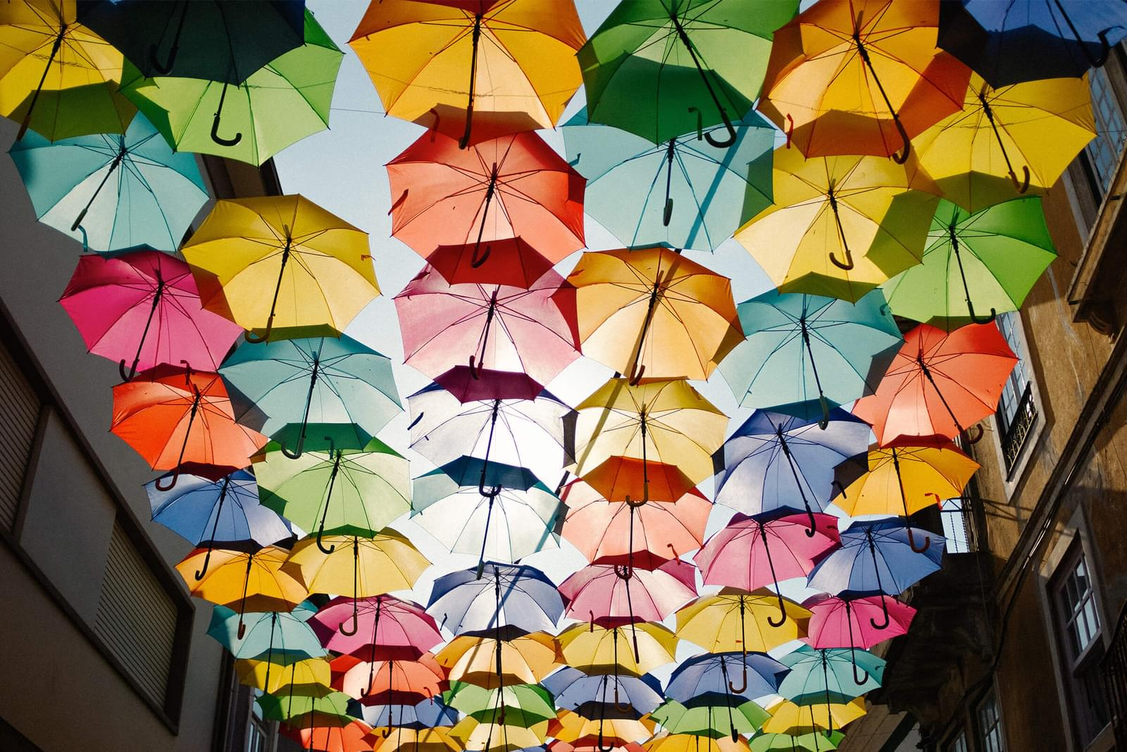 a collection of multi coloured umbrellas hung in between a street