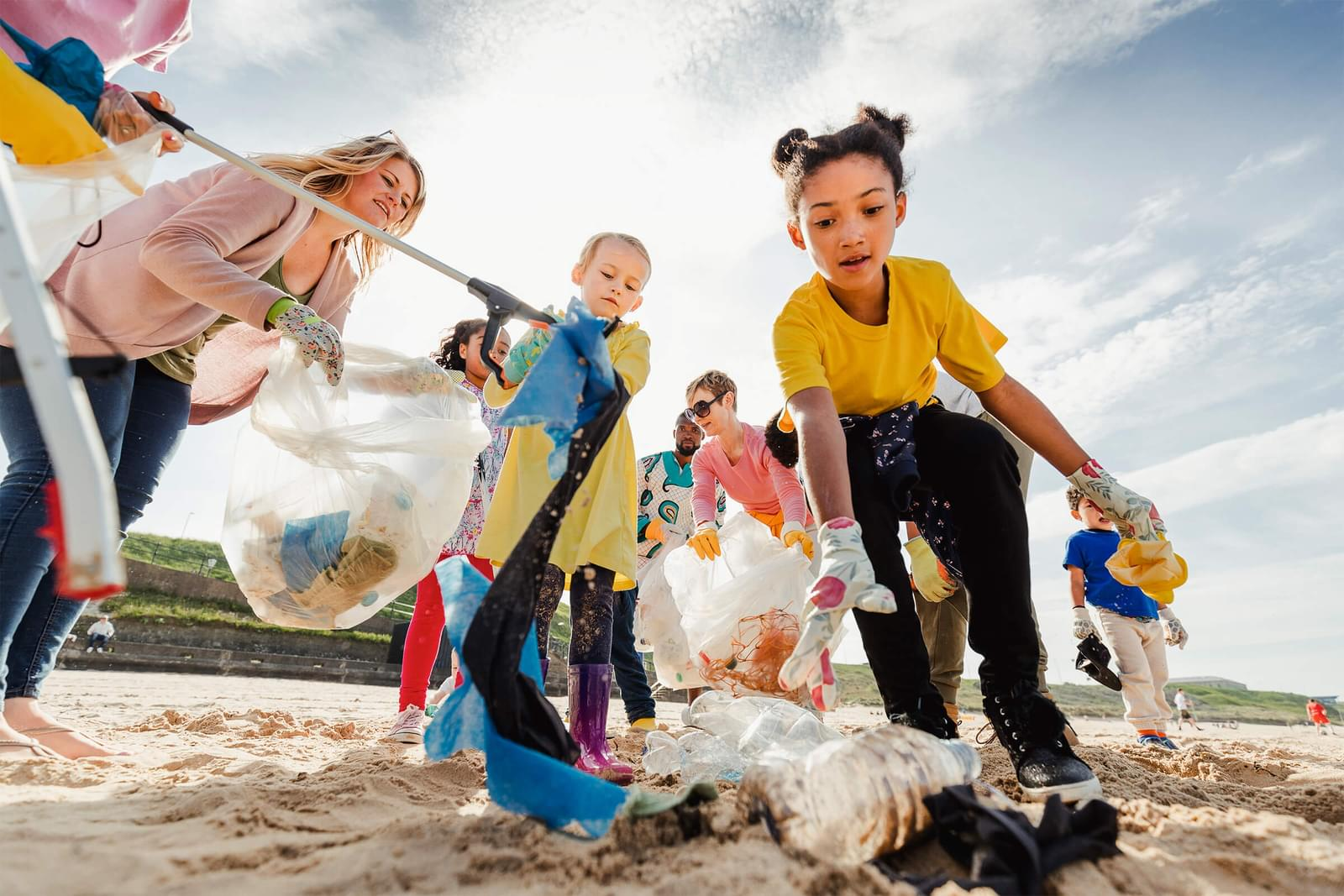 Kids walking on the beach picking up plastic